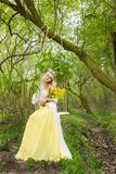 Stunning blonde sexy natural woman swing on a swing on a tree wearing a spring dress. Holding a bouquet of spring Stock Photography