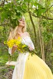 Stunning blonde sexy natural woman swing on a swing on a tree wearing a spring dress. Holding a bouquet of spring Royalty Free Stock Photo