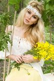 Stunning blonde sexy natural woman swing on a swing on a tree wearing a spring dress. Holding a bouquet of spring Stock Photos