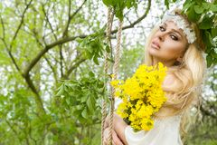 Stunning blonde sexy natural woman swing on a swing on a tree wearing a spring dress. Holding a bouquet of spring Stock Images
