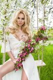 Stunning blonde sexy natural woman swing on a swing on a tree wearing a spring dress. Holding a bouquet of spring Stock Photo