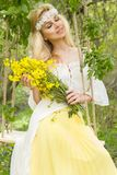 Stunning blonde sexy natural woman swing on a swing on a tree wearing a spring dress. Holding a bouquet of spring Stock Image