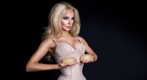 Stunning blonde woman holds in her hands silicone implants. But has a natural breasts Royalty Free Stock Image