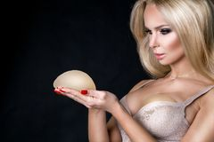 Stunning blonde woman holds in her hands silicone implants. But has a natural breasts Stock Images