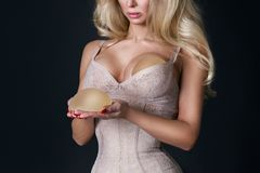 Stunning blonde woman holds in her hands silicone implants. But has a natural breasts Stock Image