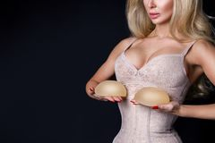 Stunning blonde woman holds in her hands silicone implants. But has a natural breasts Royalty Free Stock Images