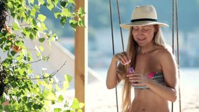 Stunning blonde woman sitting on a swing on beach stock footage
