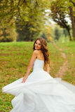 Stunning bride looks over her shoulder while whirling. On the green hill Royalty Free Stock Photo