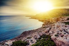 Stunning bright beautiful sunset by the sea. Rocks and azure blu Royalty Free Stock Photos