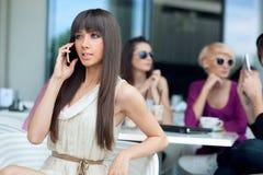 Stunning brunette beauty. Using cellphone Stock Image