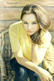 Stunning brunette beauty sitting on a chair Royalty Free Stock Photography