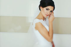 Stunning brunette bride looks tender posing in white room Royalty Free Stock Photo