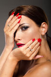 Stunning brunette with hands on her face. On a grey background. She has bright red lips and nails Stock Photography