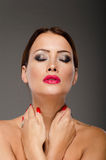 Stunning brunette with hands on her neck. On a grey background. She has bright red lips and nails Royalty Free Stock Photography