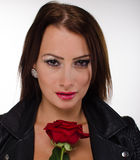Stunning brunette holding a red rose. On a grey background. She has bright red lips and nails Stock Photos