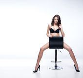 Stunning brunette. Sitting and posing on a chair Royalty Free Stock Image