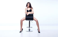Stunning brunette. Sitting and posing on a chair Royalty Free Stock Photography