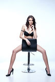 Stunning brunette. Sitting and posing on a chair Stock Photography
