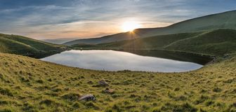 Stunning colorful Summer sunrise landscape by Llyn Cwm Llwch lak. Beautiful Summer sunrise landscape by Llyn Cwm Llwch lake in Brecon Beacons National Park with Royalty Free Stock Images