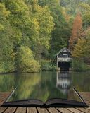 Stunning colorful vibrant Autumn Fall landscape image of boathouse on lake in forest scene coming out of pages in magical story. Beautiful colorful vibrant stock photography