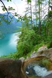 Stunning colorful waterfall falling to Konigsee known as Germany`s deepest and cleanest lake, located in Berchtesgadener National. Stunning colorful waters of stock image