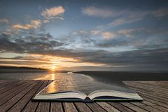 Stunning colorful Winter sunrise over low tide beach concept co. Beautiful vibrant Winter sunrise over low tide beach  concept coming out of pages in open book Stock Photos