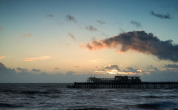 Stunning colorful Winter sunset sky above burned out pier at sea Royalty Free Stock Photo