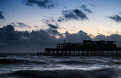 Stunning colorful Winter sunset sky above burned out pier at sea Royalty Free Stock Image