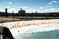 Sydney, NSW/Australia: Bondi Beach with the Iceberg Pool in the background and the surfers stock image