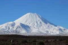 Stunning cone of Ngauruhoe volcano in winter. Stunning cone of Ngauruhoe volcano whole under snow in winter time during beautiful sunny day in Tongariro National Royalty Free Stock Photo