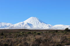Stunning cone of Ngauruhoe volcano in winter. Stunning cone of Ngauruhoe volcano whole under snow in winter time during beautiful sunny day in Tongariro National Stock Image