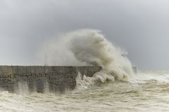 Stunning dangerous high waves crashing over harbor wall during windy Winter storm at Newhaven on English coast. Stunning waves crashing over harbor wall during stock images