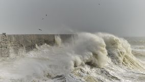 Stunning dangerous high waves crashing over harbor wall during windy Winter storm at Newhaven on English coast. Stunning waves crashing over harbor wall during stock photography