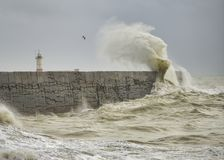 Stunning dangerous high waves crashing over harbor wall during windy Winter storm at Newhaven on English coast. Stunning waves crashing over harbor wall during royalty free stock photography
