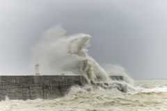 Stunning dangerous high waves crashing over harbor wall during windy Winter storm at Newhaven on English coast. Stunning waves crashing over harbor wall during stock image