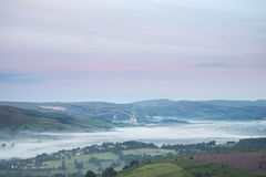 Beautiful dawn sunrise landscape image from Higger Tor towards H. Stunning dawn sunrise landscape image from Higger Tor towards Hope Valley layered in fog in Stock Images
