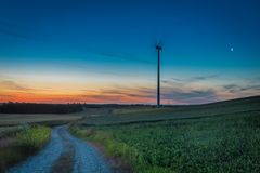 Stunning dusk over field with wind turbines Royalty Free Stock Photos