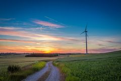 Stunning dusk over field wind turbines in summer Royalty Free Stock Image