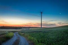 Stunning dusk over green field and wind turbines Stock Photos