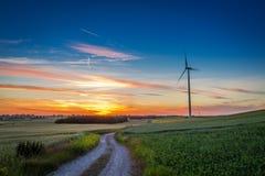 Stunning dusk over green field wind turbines in summer Stock Photos