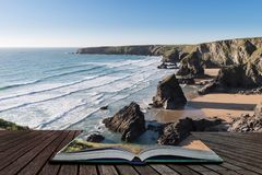 Stunning dusk sunset landscape image of Bedruthan Steps on West Cornwall coast in England coming out of pages of open story book. Beautiful dusk sunset landscape stock photo