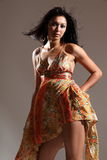 Stunning fashion model wearing gold pattern dress Royalty Free Stock Photo