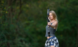 Stunning female archer in action. Stunning young blonde woman archer stands ready to fire an arrow from her compound bow - flannel shirt tied off around her Royalty Free Stock Photography