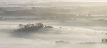 Stunning foggy English rural landscape at sunrise in Winter with stock image