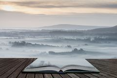 Stunning foggy English rural landscape at sunrise in Winter with layers rolling through the fields coming out of pages in magical. Beautiful foggy English royalty free stock photo