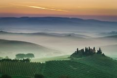 Stunning foggy green fields at sunset in Tuscany, Italy. Europe royalty free stock photo