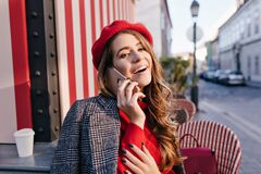Stunning french woman with long brown hair talking on phone in outdoor cafe. Portrait of resting curly girl in red beret