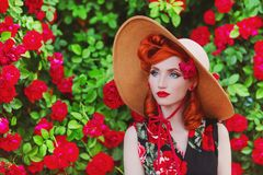 Stunning girl with red lips in dress with a print of roses on a beautiful summer background. Young redhead model in hat on a backg. Round stunning roses bush stock image