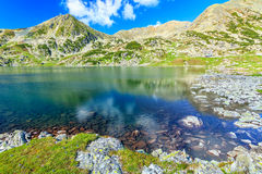 Stunning glacier lake and colorful stones,Retezat mountains,Transylvania,Romania. Wonderful tarn in the high mountains,Bucura lake,Retezat National Park royalty free stock photography