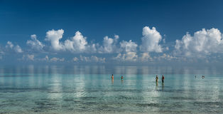 Stunning gorgeous, amazing beautiful tranquil inviting ocean view with white fluffy clouds reflected in water Stock Photo